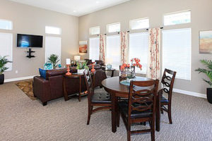 Resident lounge with seating area with table, couches, television, bright windows, and decorations