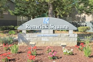 """Renwick Square stone sign, """"Senior Rental Community"""" surrounded with mulch and flowers"""